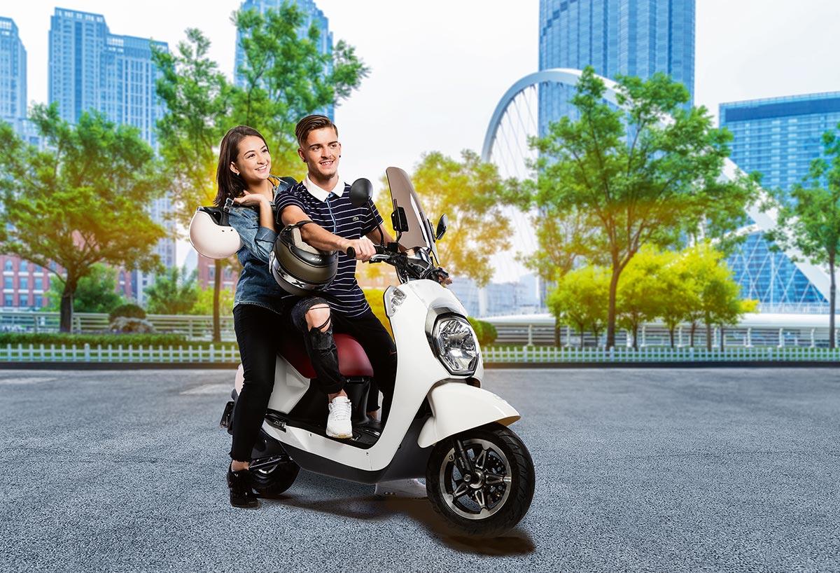 Junger Mann und junge Frau auf einem coolen Eletroroller.